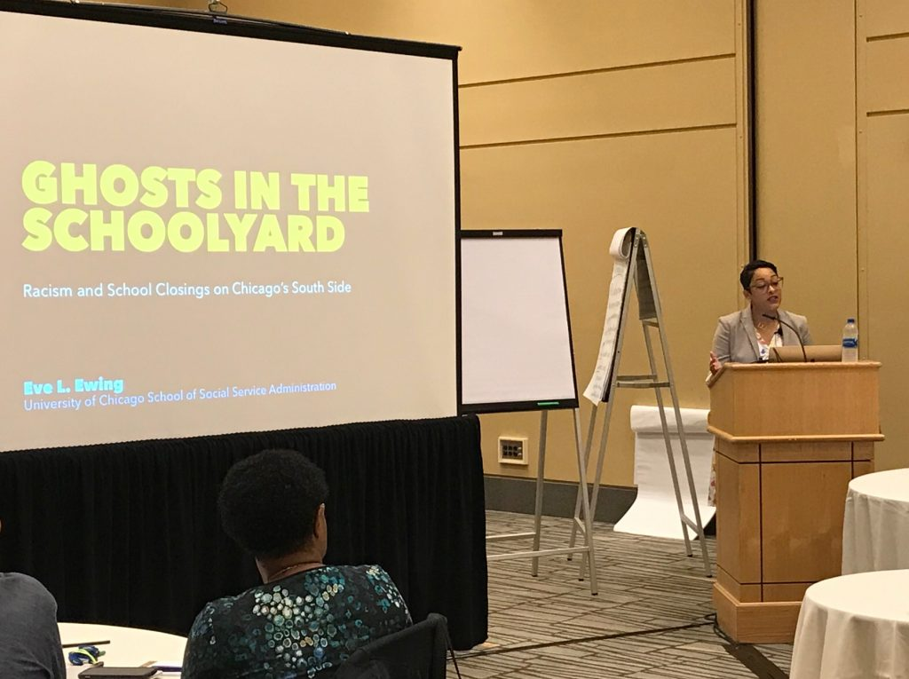 "Eve L. Ewing presents from the podium at a gathering of StriveTogether communities. The slide shares the title of her book ""Ghosts in the Schoolyard: Racism and School Closings on Chicago's South Side."""